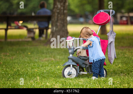 Fourteen months old baby girl making her first steps; climbing on the tricycle in the park - Stock Photo