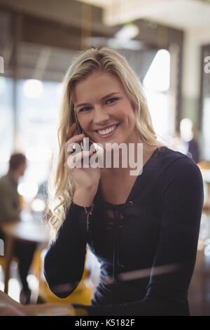 Portrait of smiling young blond woman talking on mobile phone while sitting at cafe - Stock Photo
