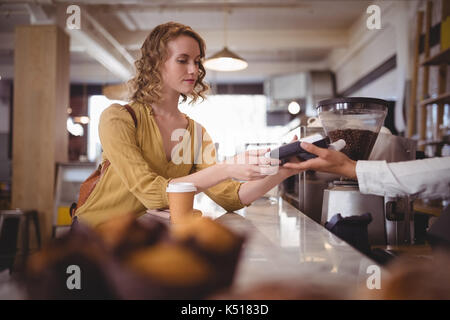 Young female customer paying through card at counter in coffee shop - Stock Photo