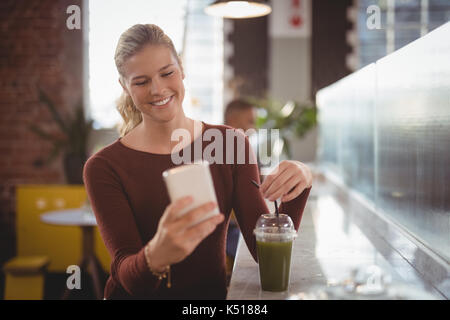 Smiling young blond woman using smartphone while sitting with drink at counter in coffee shop - Stock Photo