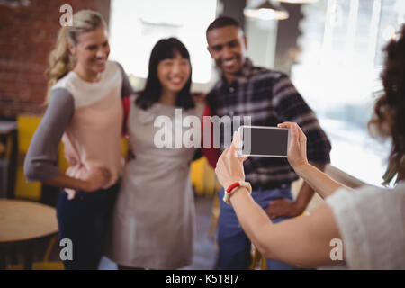 Cropped image of woman photographing friends from smartphone at coffee shop - Stock Photo