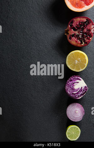Overhead view of various fruits and vegetables arranged on gray slate - Stock Photo