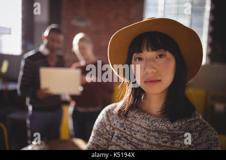 Portrait of confident young woman wearing hat while standing against colleagues in coffee shop - Stock Photo