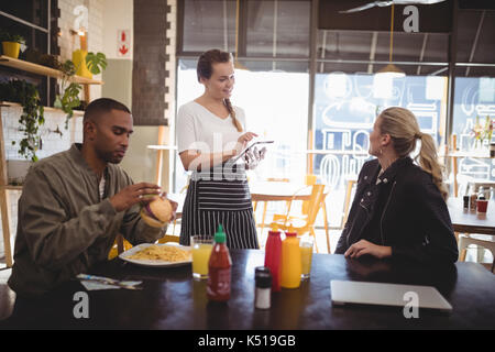 Young woman ordering food to waitress while sitting with male friend at cafe - Stock Photo