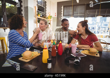 Cheerful young friends sharing food at table in coffee shop - Stock Photo