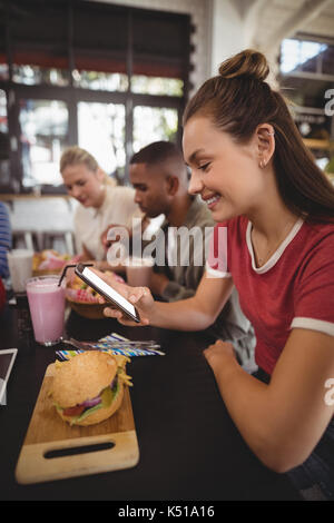 Side view of smiling young woman text messaging while sitting with burger at table in coffee shop - Stock Photo