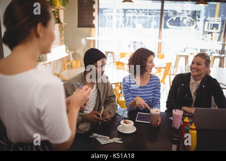 Smiling woman siting with friends ordering food to waitress at cafe - Stock Photo