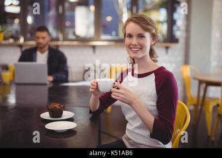 Portrait of smiling young woman holding coffee cup while sitting at table in cafe - Stock Photo