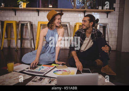 Smiling young designers sitting with sheets on floor at coffee shop - Stock Photo