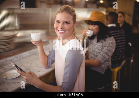 Portrait of smiling young woman drinking coffee while using mobile phone at counter in coffee shop - Stock Photo