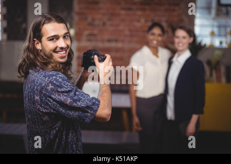 Portrait of smiling young photographer photographing female colleagues at coffee shop - Stock Photo