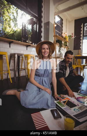 Portrait of smiling young female professional sitting with male colleague on floor at coffee shop - Stock Photo