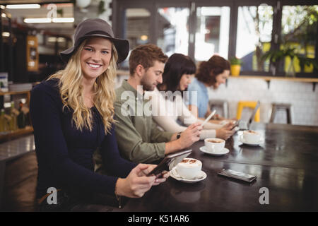 Portrait of smiling young woman sitting with friends at table in cafe - Stock Photo