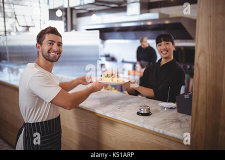 Portrait of smiling female chef and waiter holding plate at counter in coffee shop - Stock Photo