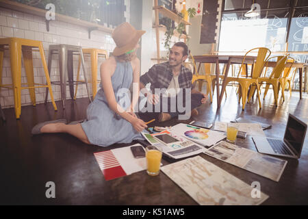Smiling young professionals sitting with sheets and technologies on floor at coffee shop - Stock Photo
