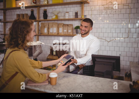 Smiling young woman paying through card to waiter at counter in coffee shop - Stock Photo