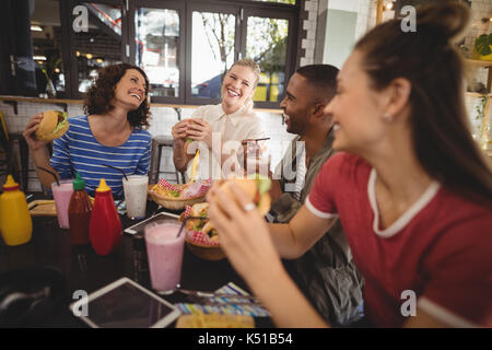 Cheerful young friends sitting with food and drink at table in coffee shop - Stock Photo