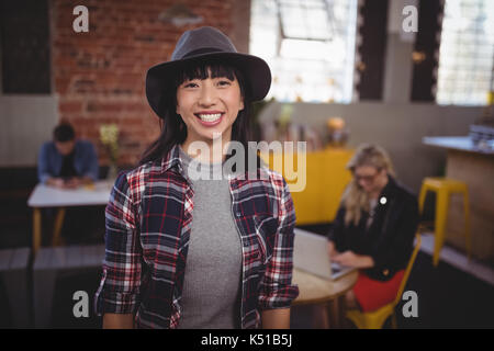 Portrait of smiling young woman wearing hat standing at coffee shop - Stock Photo