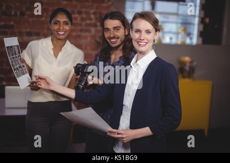 Portrait of smiling young creative team discussing collage at coffee shop - Stock Photo