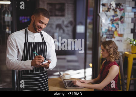 Smiling young waiter writing in notepad while standing against female customer at coffee shop - Stock Photo