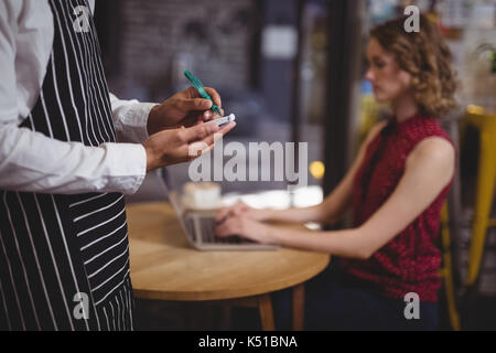 Midsection of waiter writing on notepad against female customer sitting at table in coffee shop - Stock Photo