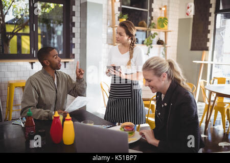 Young man ordering food to waitress while sitting with female friend at cafe - Stock Photo