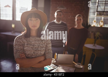 Portrait of woman wearing hat standing with arms crossed against colleagues at coffee shop - Stock Photo
