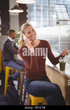 Happy beautiful blond woman talking on celllphone while sitting at counter with drink in coffee shop - Stock Photo