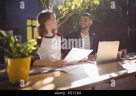 Smiling young creative professionals talking while sitting with laptop at table in coffee shop - Stock Photo