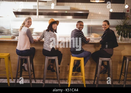 Rear view portrait of smiling young friends sitting on stools at counter in coffee shop - Stock Photo
