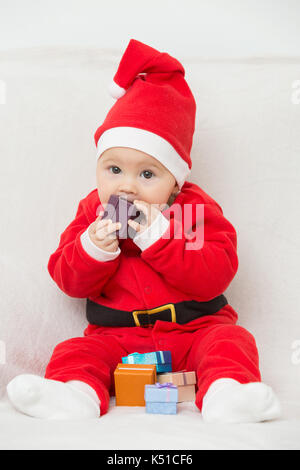 Seven months old baby girl in Santa Claus dress sitting on a white blanket, playing with little gifts and putting - Stock Photo