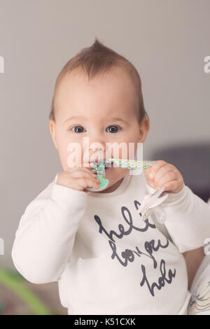 Eight months old baby girl bringing her pacifier to her mouth and sucking it - Stock Photo