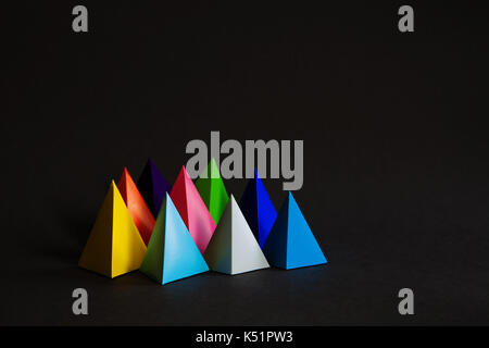 Minimalistic colorful composition abstract geometric shape figures on black background. Three-dimensional pyramid - Stock Photo