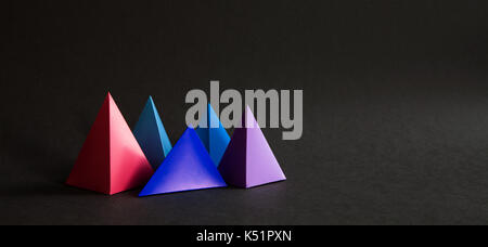 Abstract colorful geometrical composition. Three-dimensional prism pyramid objects on black paper background. Pink - Stock Photo