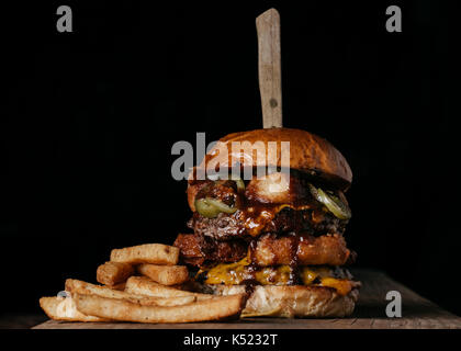Double Meat Burger with fried onion rings, cheese and pickled jalapeños - Stock Photo