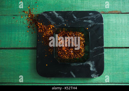 Crushed red pepper in bowl on wooden table - Stock Photo