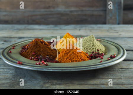 Close-up of various spices in plate on wooden table - Stock Photo