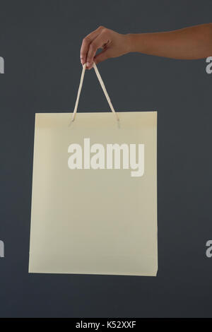 Cropped hand of female customer holding shopping bag against gray background - Stock Photo
