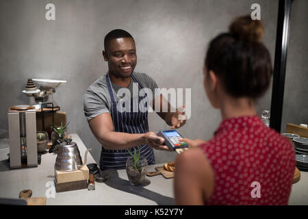 Customer making payment through credit card at counter in cafe - Stock Photo