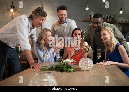 Woman receiving birthday gift form her friends in restaurant - Stock Photo