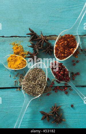 Overhead view of various spices on wooden table - Stock Photo