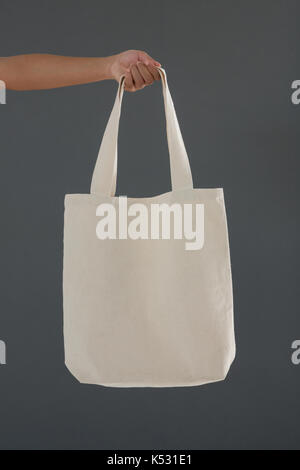 Cropped hand of female customer holding shoulder bag against gray background - Stock Photo