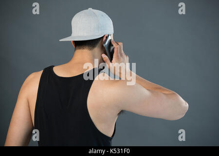 Rear view of man talking on mobile phone against grey background - Stock Photo