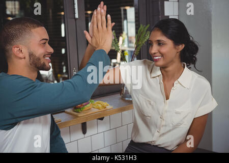 Happy young couple giving high-five while sitting in cafe - Stock Photo
