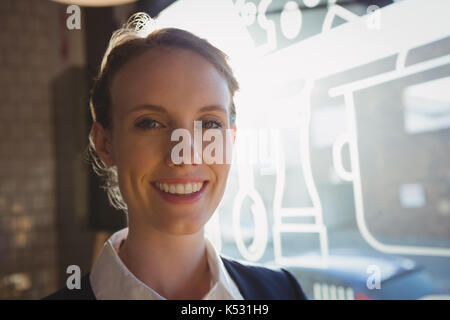 Portrait of smiling female owner in cafe - Stock Photo