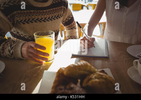 Mid section of woman with man writing on book while sitting at table in cafe - Stock Photo