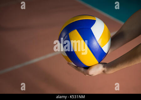 Cropped hands of player with volleyball at court - Stock Photo