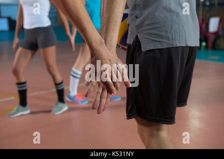 Cropped image of volleyball player holding hand with teammate at court - Stock Photo