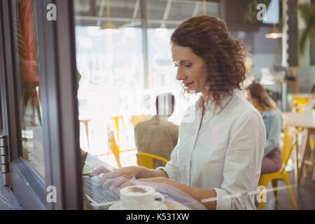 Young woman using laptop seen through glass window at cafe - Stock Photo