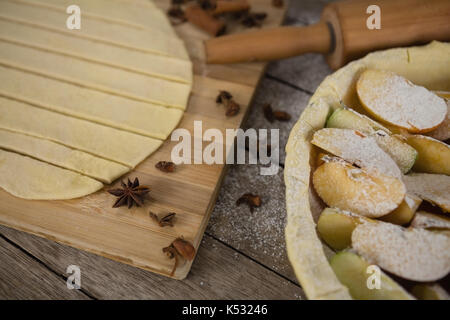 High angle view of pastry dough stripes on cutting board with apple in baking pan on table - Stock Photo